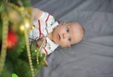 O bebê com olhos azuis aproxima a árvore de Natal Ano novo imagem de stock royalty free