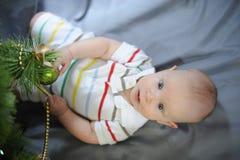 O bebê com olhos azuis aproxima a árvore de Natal Ano novo fotografia de stock