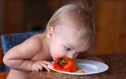 O bebê come o caqui maduro fresco na placa branca Imagens de Stock Royalty Free
