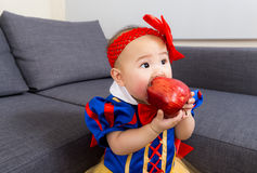 O bebê come a maçã com molho de partido do Dia das Bruxas fotografia de stock royalty free