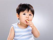 O bebê come o biscoito e olha afastado imagens de stock