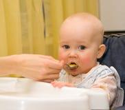 O bebê come o papa de aveia de uma colher Foto de Stock