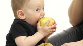 O bebê come uma maçã, ao lado de sua mãe Fundo branco Movimento lento Fim acima vídeos de arquivo
