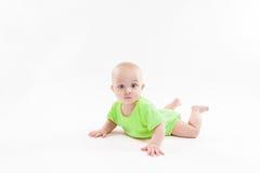 O bebê curioso bonito encontra-se em seu estômago e em olhar a câmera imagens de stock