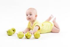 O bebê curioso bonito encontra-se em seu estômago e em olhar a câmera fotos de stock