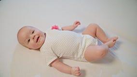 O bebê curioso pequeno está colocando em uma cobertura branca e está olhando ao redor imagens de stock