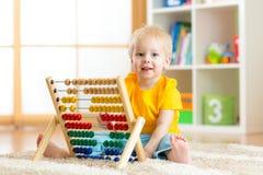 O bebê da criança em idade pré-escolar aprende contar Criança bonito que joga com brinquedo do ábaco Rapaz pequeno que tem o dive fotos de stock royalty free