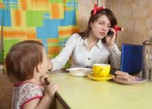 O bebê de alimentação da mulher de negócios e fala pelo móbil Imagens de Stock Royalty Free