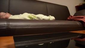 O bebê de limpeza do whille da tabela do coffe da mãe está dormindo no sofá