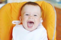 O bebê de riso no babador senta-se na cadeira do bebê Fotografia de Stock Royalty Free
