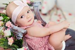 O bebê de sorriso de olhos bem abertos muito bonito pequeno em um vestido cor-de-rosa é i foto de stock
