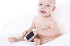 O bebê de sorriso está aprendendo tratar um telefone foto de stock