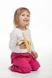 O bebê de sorriso está comendo a banana madura Foto de Stock