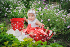 O bebê de sorriso está sentando-se na grama verde e nas flores com dott Fotos de Stock
