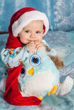 O bebê de sorriso no chapéu e em guardar do Natal um brinquedo morde-a Imagem de Stock Royalty Free