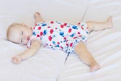 O bebê dorme em uma folha branca recém-nascida, menina caiu adormecido na cama imagens de stock