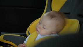 O bebê dorme no carro na maneira Criança de sono na cadeira traseira no carro video estoque