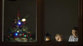 O bebê e o irmão olham a janela com lâmpada, árvore de Natal no fundo, esperando a primeira celebração vídeos de arquivo