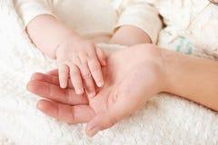 O bebê e a mãe entregam o close up, conceito de maternidade feliz imagem de stock royalty free