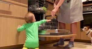 O bebê e a mãe põem os pratos na máquina de lavar louça vídeos de arquivo
