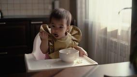 O bebê em um babador verde está comendo o papa de aveia do bebê da tabela com uma colher