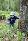 O bebê em um chapéu e em calças de brim surpreendeu a cara Bebê 9 meses que exploram a grama e as árvores da floresta Primeiramen imagens de stock