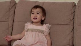 O bebê em um vestido bonito senta-se em um sofá cinzento macio e nos risos que olham acima vídeos de arquivo