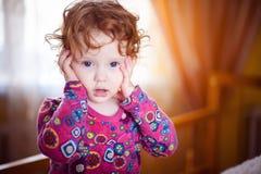 O bebê em um vestido vermelho com a admiração olha fotografia de stock