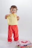 O bebê encantador na calças vermelha tenta sobre a roupa imagem de stock
