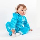 O bebê encantador no azul senta-se no assoalho que olha afastado fotos de stock