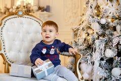O bebê encantador pequeno na camiseta azul senta-se em uma cadeira em torno da Foto de Stock