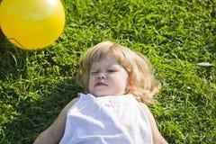 O bebê encontra-se em uma grama imagens de stock royalty free
