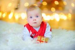 o bebê engraçado com os olhos azuis grandes, encontrando-se no assoalho com uma caixa de presente pequena, olhando na surpresa na fotos de stock