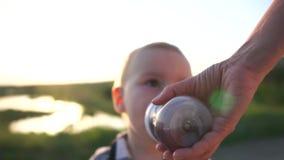 O bebê está bebendo de uma garrafa de bebê que a mamã sustente no por do sol no movimento lento filme