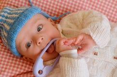 O bebê está jogando com um chocalho Imagem de Stock