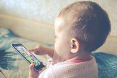 O bebê está jogando com um smartphone Imagem de Stock Royalty Free