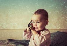 O bebê está jogando com um smartphone Foto de Stock