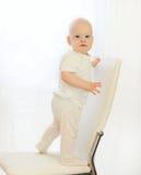 O bebê está na cadeira em casa e olha na câmera Imagem de Stock Royalty Free