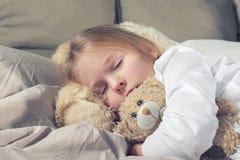 O bebê está rapidamente adormecido abraçando um urso de peluche Menina com cabelo louro na cama imagem de stock royalty free