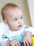 O bebê está sentando-se em uma cadeira do bebê Fotos de Stock Royalty Free