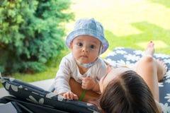 O bebê eyed azul pequeno veste o tampão do sol nos braços da mamã nova que colocam na cadeira de plataforma durante o dia ensolar imagens de stock