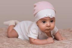 O bebê fêmea pequeno bonito bonito encantador com mordentes gordos rasteja na cama, olha inocentemente em algo, sendo impertinent Foto de Stock Royalty Free