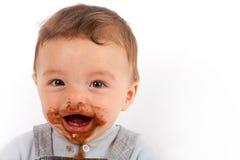 O bebê feliz come o chocolate Fotos de Stock Royalty Free