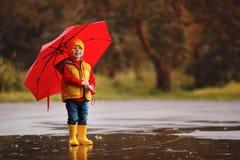 O bebê feliz da criança com botas de borracha e o guarda-chuva saltam no pudd foto de stock