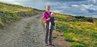O bebê feliz da posse da mãe 7 meses suporta sobre no portador de bebê que anda em montanhas Carpathian fotos de stock