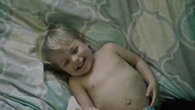 O bebê feliz na cama joga com mamã Imagens de Stock