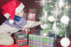 O bebê feliz próximo decorou a árvore de Natal com muitos caixa de presente Imagem de Stock Royalty Free