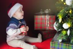 O bebê feliz próximo decorou a árvore de Natal com muitos caixa de presente Imagem de Stock