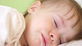 O bebê fricciona seus olhos e tentativas para dormir A criança pequena cai adormecido em sua ucha filme