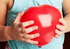 O bebê guarda coração vermelho o balão dado forma Imagens de Stock Royalty Free